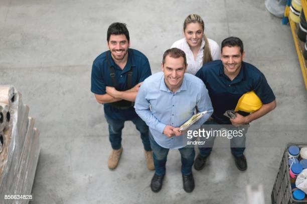Glückliche Gruppe von Menschen in Lateinamerika arbeiten in einem Lagerhaus