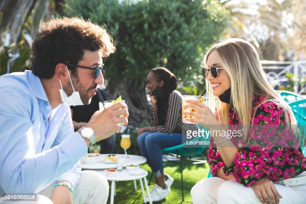 happy group of multi ethnic friends enjoying some refreshing drinks wearing protective face mask - five people stock pictures, royalty-free photos & images