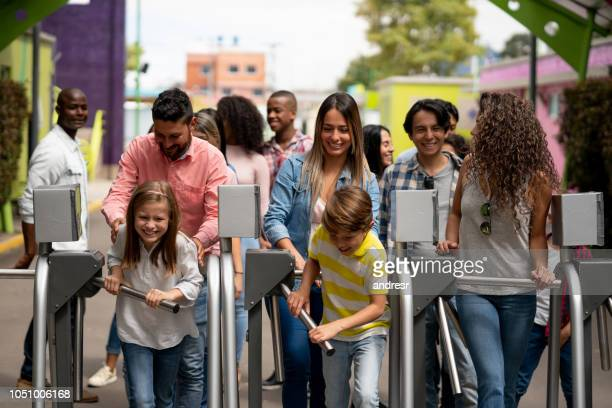 gelukkig groep van mensen aankomen op een pretpark - portiek stockfoto's en -beelden