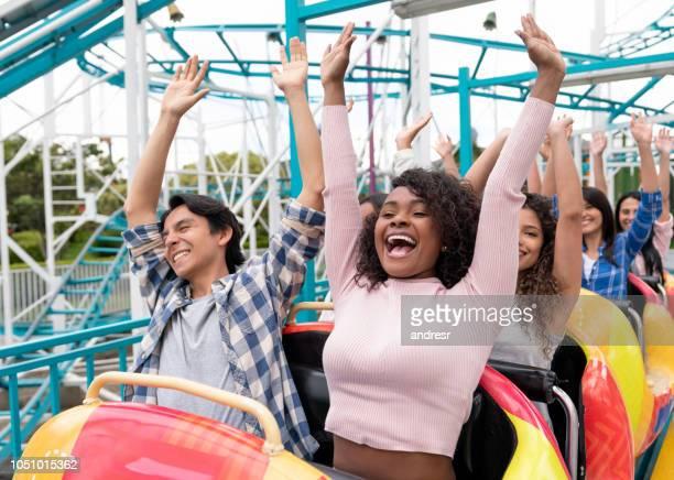 happy group of people having fun in a rollercoaster at an amusement park - grupo médio de pessoas imagens e fotografias de stock
