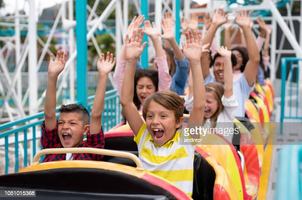 happy group of people having fun in a rollercoaster at an amusement park - amusement park stock pictures, royalty-free photos & images