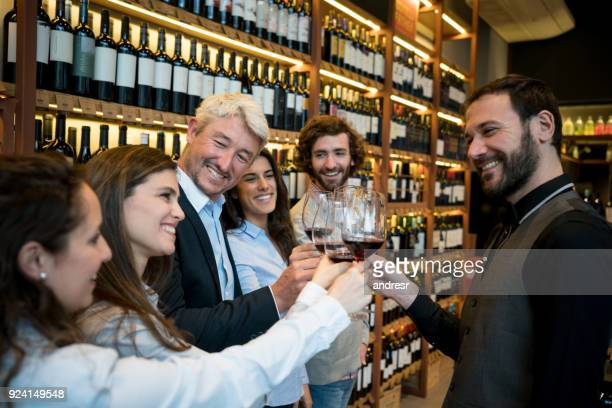 Happy group of people toasting and tasting wines at a winery