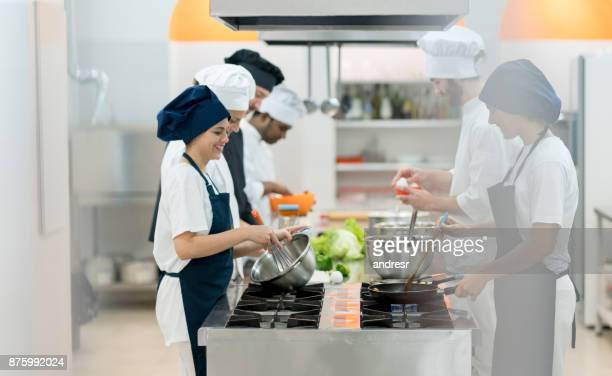 Happy group of people working at an industrial kitchen smiling
