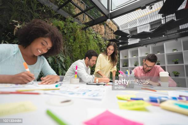 Happy group of people working together at a creative office