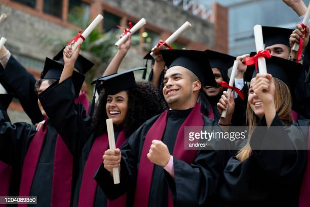 happy group of students celebrating on their graduation day - alumni stock pictures, royalty-free photos & images