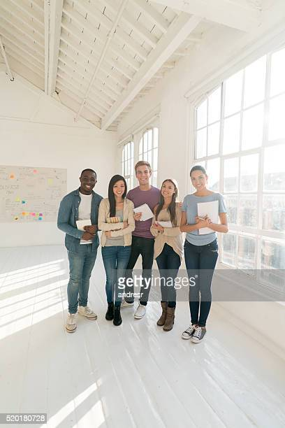Happy group of students holding notebooks
