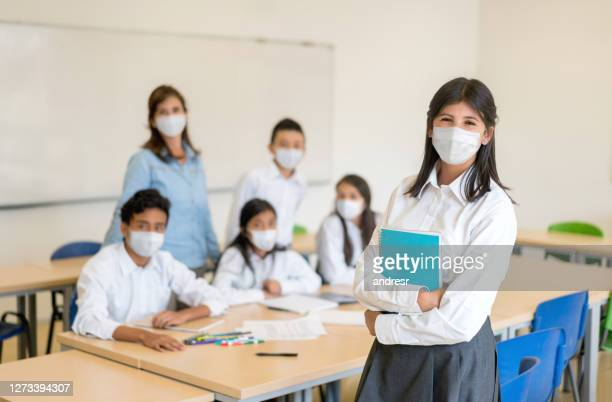 happy group of students in class at the school wearing facemasks - uniform stock pictures, royalty-free photos & images
