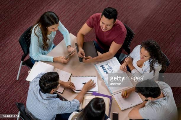 feliz grupo de alunos estudando na biblioteca - grupo médio de pessoas - fotografias e filmes do acervo