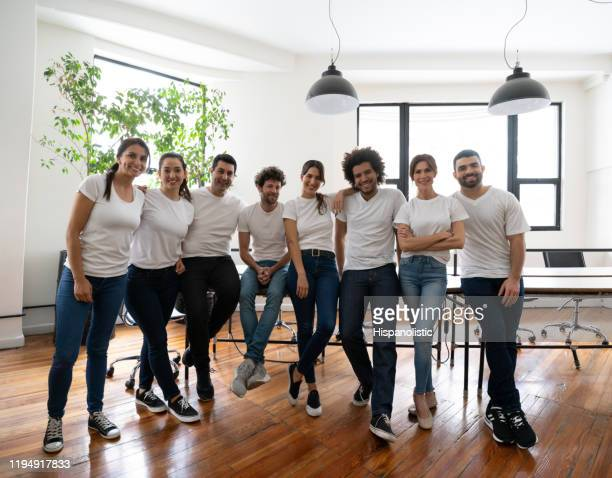 happy group of volunteers at an office all wearing white t-shirts smiling at camera - white t shirt stock pictures, royalty-free photos & images