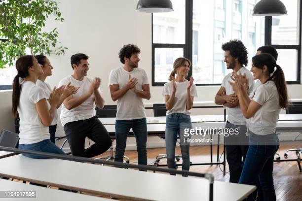 非常に陽気に微笑むアフリカ系アメリカ人男性に拍手を送る会議中のボランティアの幸せなグループ - 非営利団体 ストックフォトと画像