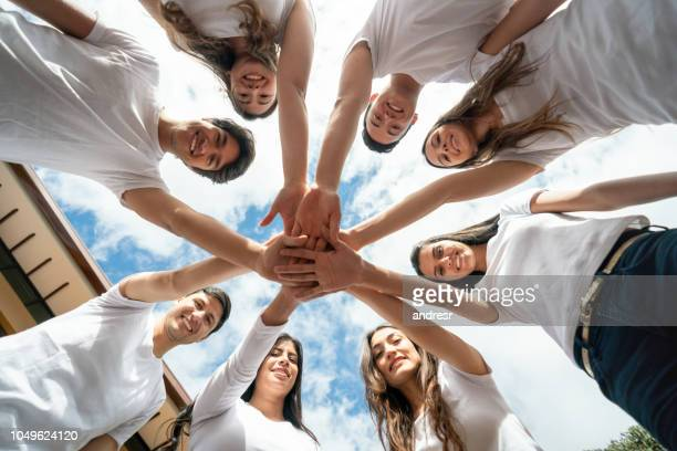 happy group of volunteers with hands together in the middle - humanitarian aid stock pictures, royalty-free photos & images