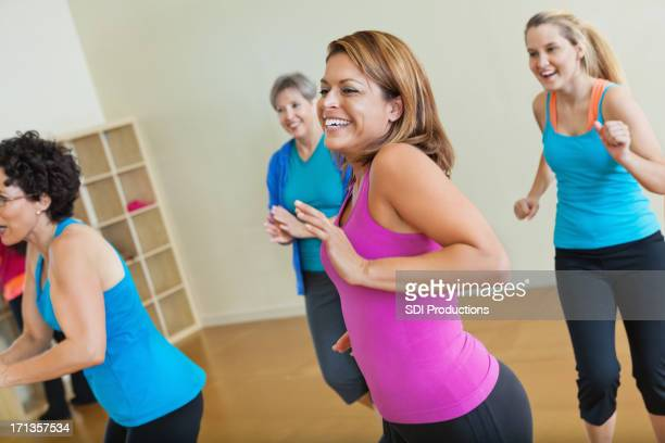 Happy group of women exercising together in fitness class