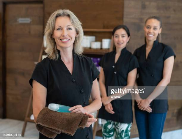 happy group of women working at a spa - beautician stock pictures, royalty-free photos & images