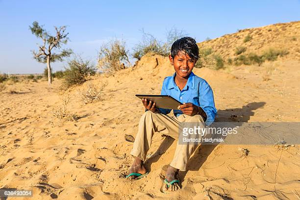 Happy Gypsy Indian young boy using digital tablet, India