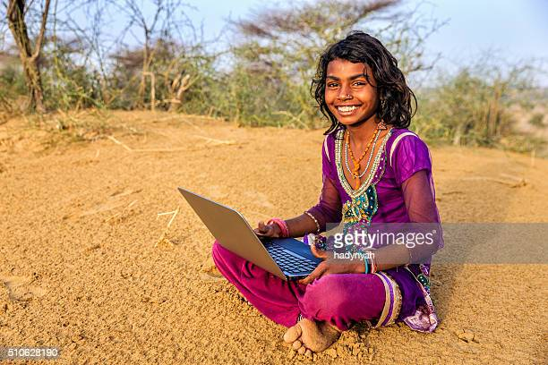 happy gypsy indian young girl using laptop, india - developing countries stock photos and pictures