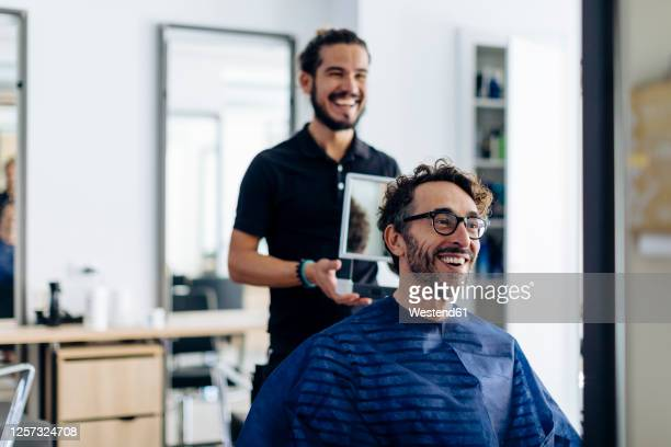 happy hairdresser showing haircut to client in mirror at salon - hairdresser stock pictures, royalty-free photos & images