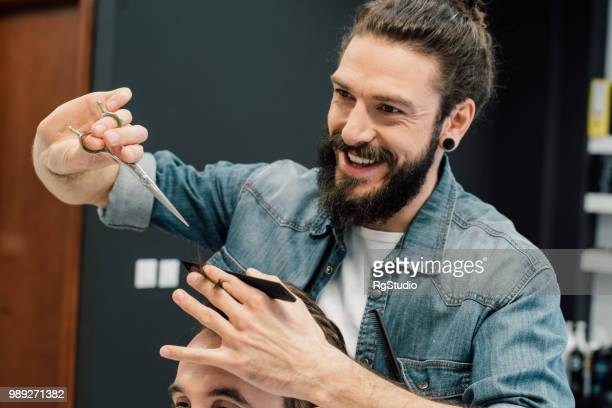 happy hairdresser with a man bun is giving a haircut - man bun stock pictures, royalty-free photos & images