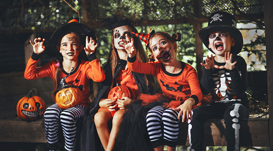 happy Halloween! a group of children in suits and with pumpkins in forest 1026635418