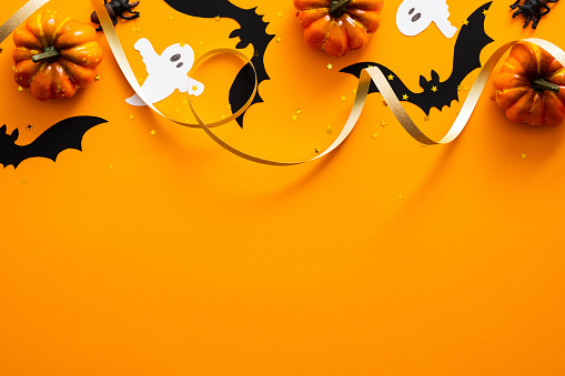 Happy halloween holiday concept. Halloween decorations, pumpkins, bats, ghosts on orange background. Halloween party greeting card mockup with copy space. Flat lay, top view, overhead. 1171184656