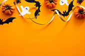 Happy halloween holiday concept. Halloween decorations, pumpkins, bats, ghosts on orange background. Halloween party greeting card mockup with copy space. Flat lay, top view, overhead.