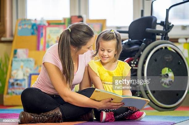 Happy Handicap Girl Reading with Her Caregiver