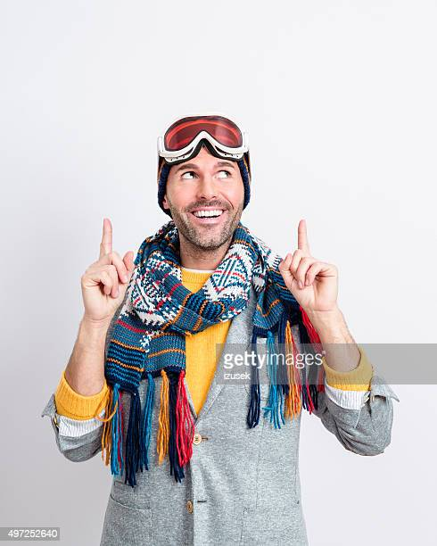 Happy handsome man in winter outfit pointing at copy space