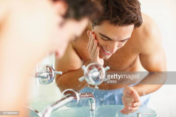 Happy handsome man washing his face at the sink
