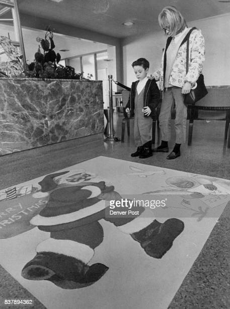 Happy Healthy Christmas A sand painting of Santa Claus decorates the lobby of Children's Hospital E 19th Ave and Downing St Admiring it are Randall...