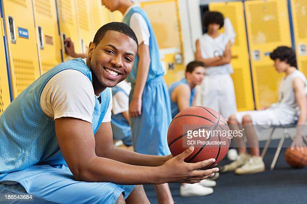 Happy high school basketball player in locker room after game