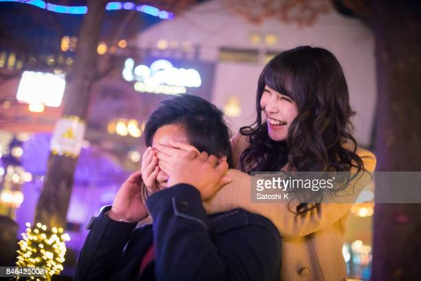 Happy high school girl blindfolding boyfriend