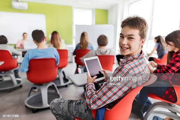 Feliz estudiante de secundaria con panel táctil en el aula.