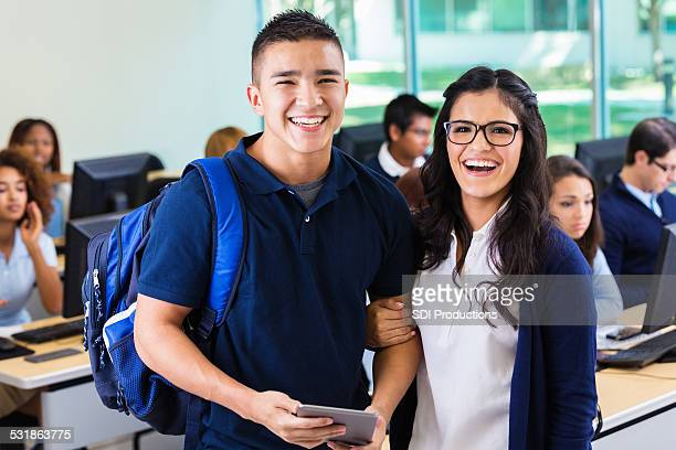 Happy high school sweetheart couple in modern classroom