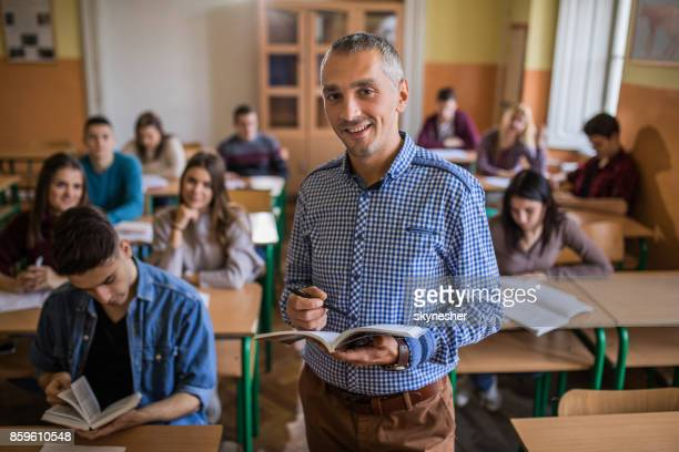 happy high school teacher looking at camera during the class in the classroom. - teacher stock pictures, royalty-free photos & images