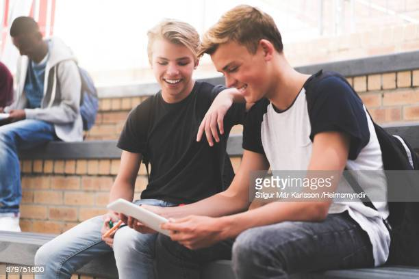 happy high school teenage students sharing tablet - 18 19 years stock pictures, royalty-free photos & images