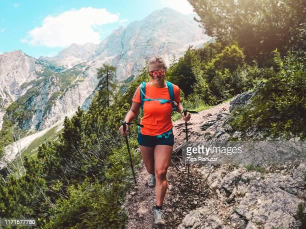 ネオンの服を着た幸せなハイカー、山のトレイルでハイキング - オレンジ色のシャツ ストックフォトと画像