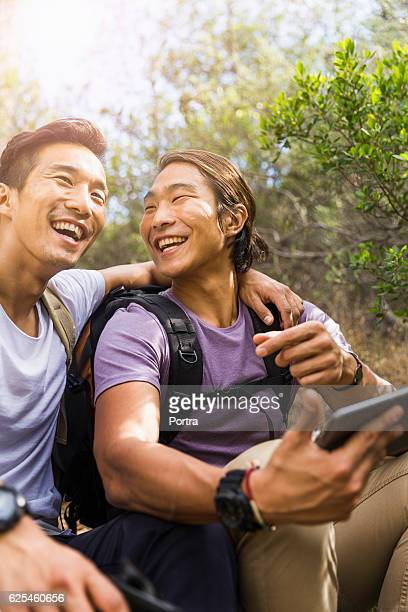 Happy hikers talking while using digital tablet