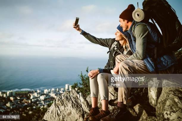 Happy hiking couple taking selfie on mountain