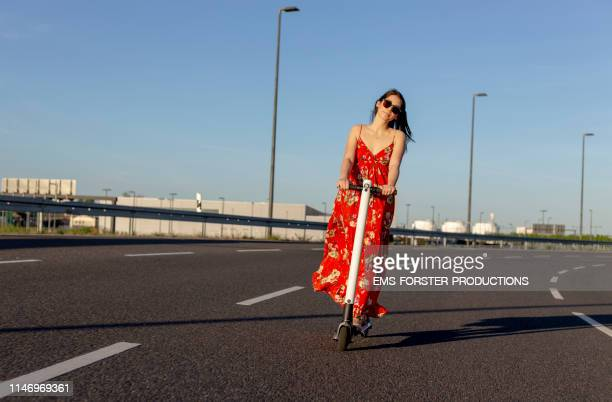 happy hippie girl is riding an electric push scooter on the street - long dress stock pictures, royalty-free photos & images