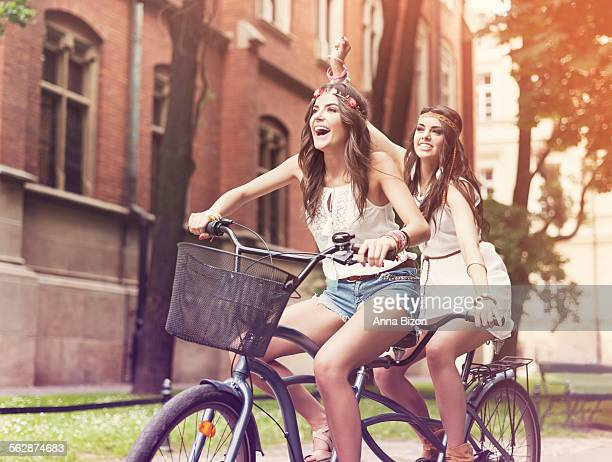 Happy hippie women riding a tandem in the park. Krakow, Poland