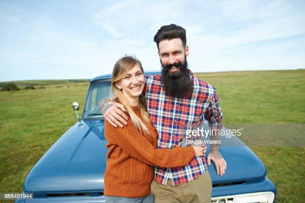 Happy hipster couple on road trip in countryside.