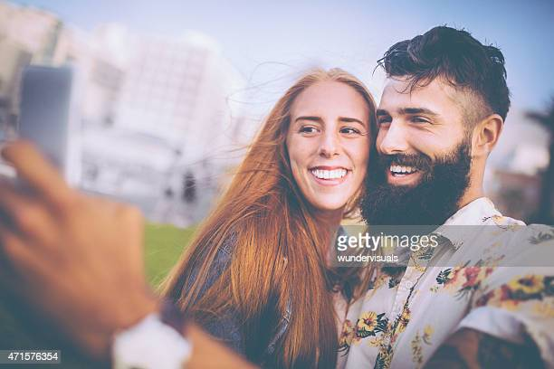 Happy hipster couple taking a selfie together