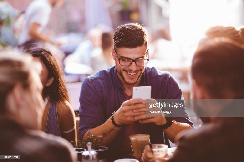 Homem feliz hipster no café SMS no telemóvel : Foto de stock