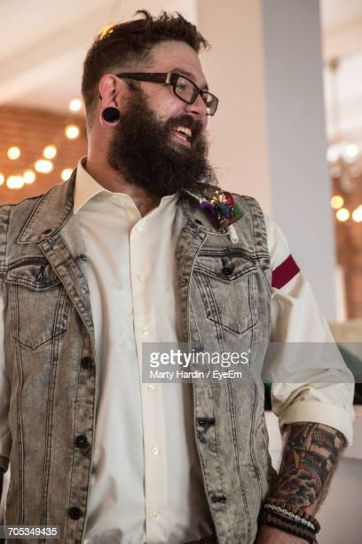 happy hipster standing in illuminated room - marty hardin stock photos and pictures