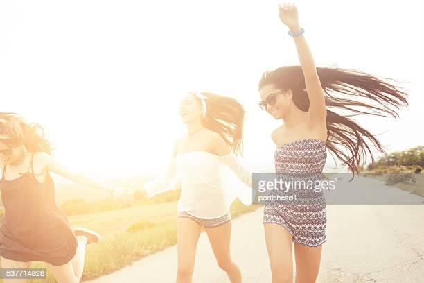 Happy hipster women holding hands and dancing on the road