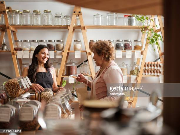 happy hispanic employee and customer smiling at each other - comida e bebida imagens e fotografias de stock
