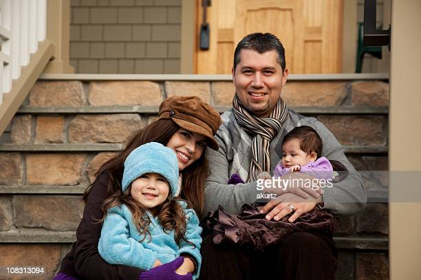 Happy Hispanic family move into their new home