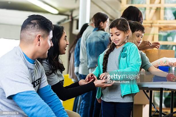 Happy Hispanic family volunteering in community food bank together