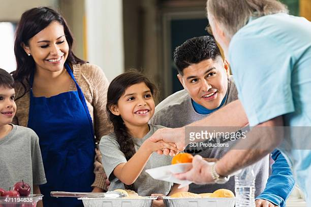 Happy Hispanic family volunteering to serve seniors together
