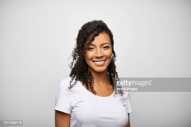 happy hispanic female against gray background - real people stockfoto's en -beelden