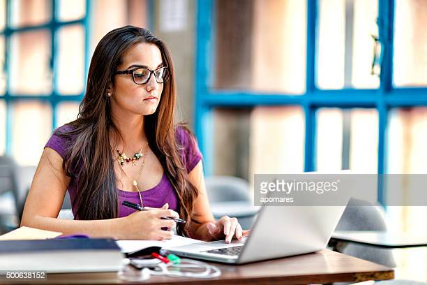 Happy Hispanic female student using laptop computer in classroom